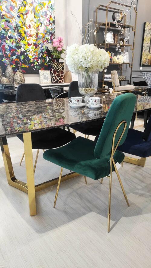 Krzesło tapicerowane obite welurem w kolorze butelkowej zieleni oraz złotymi smukłymi nogami